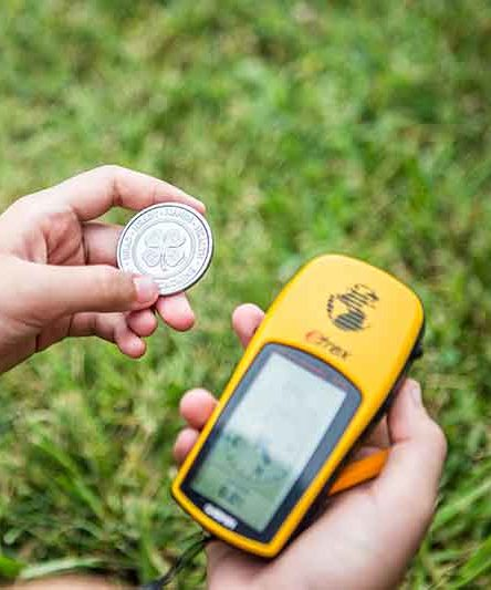 Child holding a 4H Coin and Garmin GPS