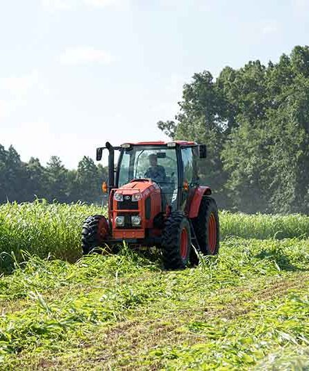 Farmer driving tractor over crops